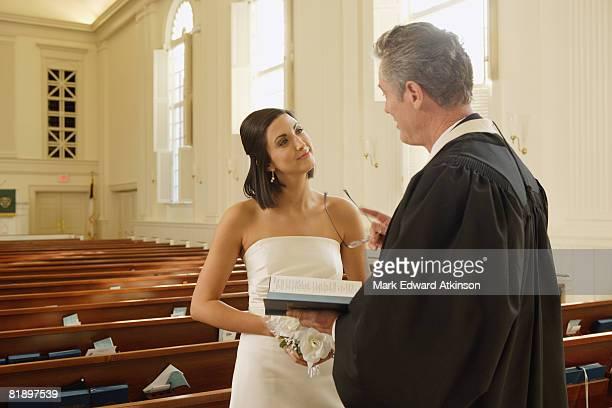priest talking to bride - prete foto e immagini stock