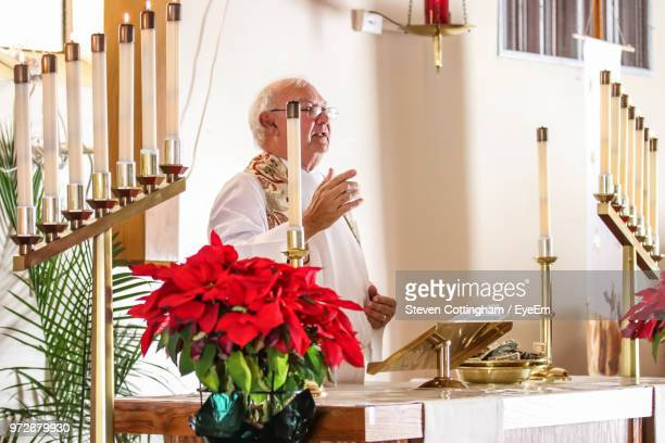 priest talking while standing in church - steven cottingham stock-fotos und bilder