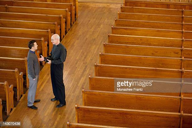 Priest talking with man in church