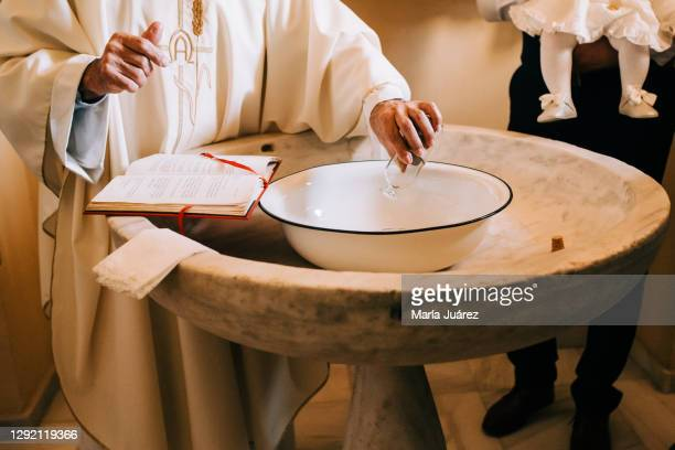 priest throws the sacred water into the baptismal font during a baby's baptism - catholic baptism stock pictures, royalty-free photos & images