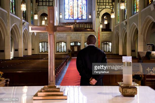 priest waiting for a sign in church - priest stock pictures, royalty-free photos & images