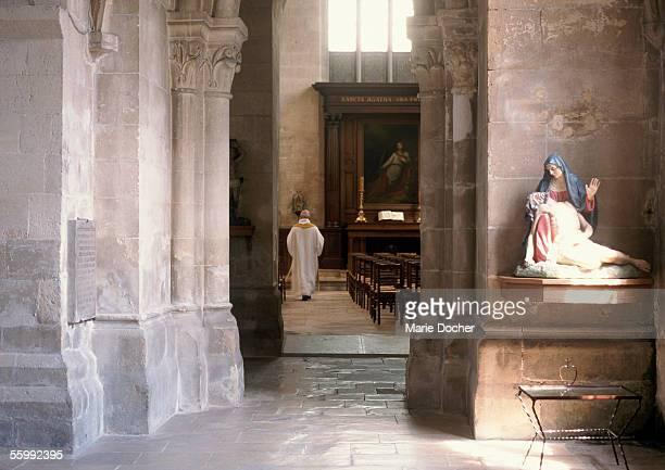 Priest walking in church, rear view