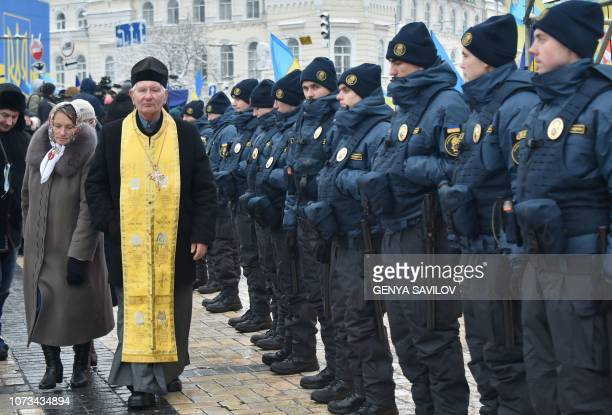 A priest walks in front of Ukrainian national guard servicemen as he arrives at Saint Sophia cathedral in Kiev on December 15 2018 ahead of a...