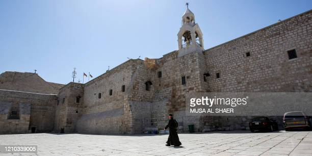 A priest walks outside the Church of the Nativity in the biblical West Bank city of Bethlehem on April 18 while the church is closed due to a...