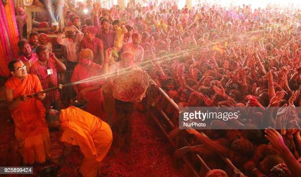 Priest water gun on devotees on the occasion of Holi festival celebration at historical Govind Dev Ji temple in Jaipur Rajasthan India on 01 March2018