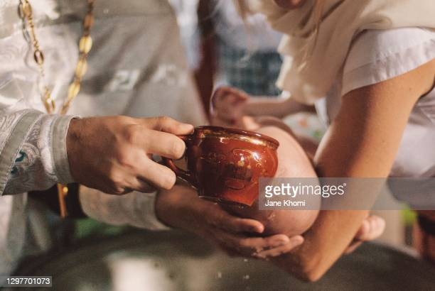 priest watering the baby, baptism - catholic baptism stock pictures, royalty-free photos & images