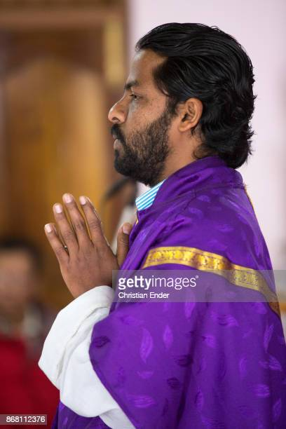 A priest wearing a colorful tunicle is praying with folded hands towards the audience while a ceremony inside a church in Kalimpong