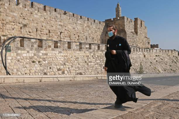 Priest, wearing a protective mask amid the COVID-19 pandemic, walks along the walls of Jerusalem's Old City on September 12, 2020. - Israel imposed...