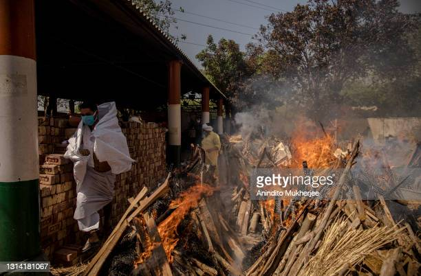 Priest who helps performing last rites, runs to avoid the heat from the multiple burning funeral pyres of patients who died of the Covid-19...