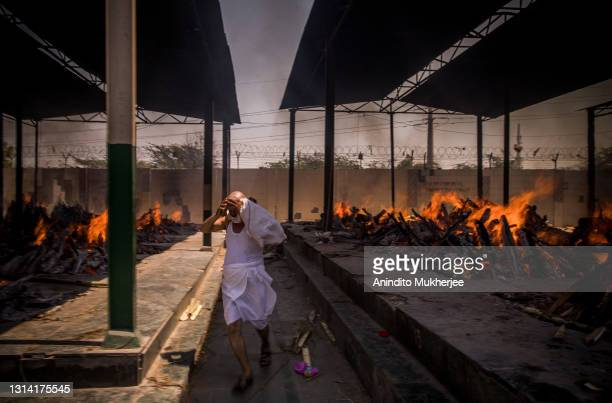 Priest who helps performing last rites, runs while covering his face amid the multiple burning funeral pyres of patients who died of the Covid-19...