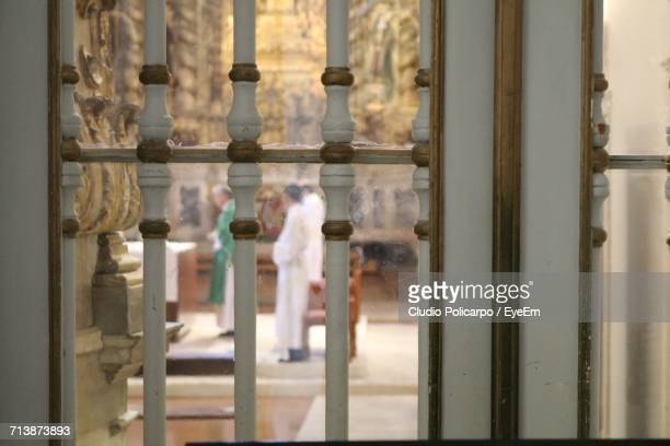 priest with people giving sermon in church seen through glass - catolicismo fotografías e imágenes de stock