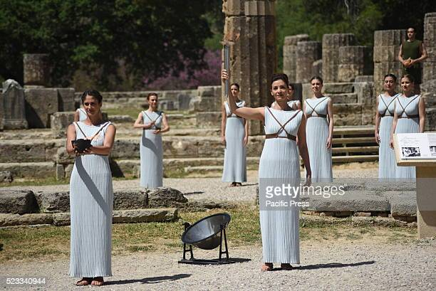 Priestesses in the ruins of the temple of Hera in Olympia holding the torch and the fire of Olympic Flame during the ceremonys rehearsal