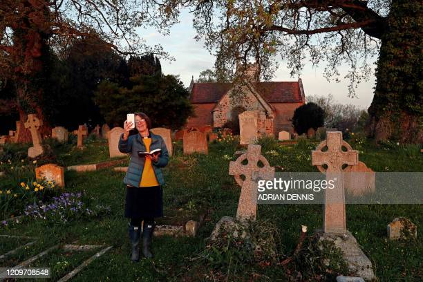 PriestinCharge Angie Smith uses her smartphone to livebroadcast an Easter Sunday service to her congregation at dawn from the churchyard of Old St...