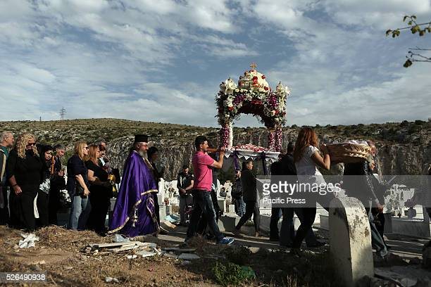 Priests and Orthodox Christians participate in the procession of the Epitaph in the cemetery of Nikea western suburb of Athens on Good Friday