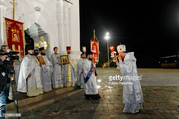 Priests are pictured outside St. Catherine's Church for a traditional procession around the temple during an Easter service on Holy Saturday,...