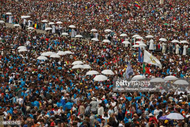 Priests carry white umbrellas along the crowds during a mass of canonization at the Sanctuary of Fatima on May 13 2017 in Fatima Portugal Pope...