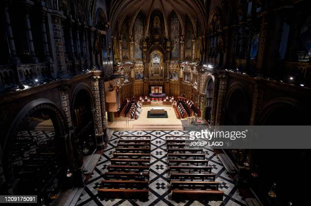 Priests celebrate the Palm Sunday Mass before empty benches on April 5 at the Santa Maria de Montserrat abbey in Monistrol de Montserrat, during a...