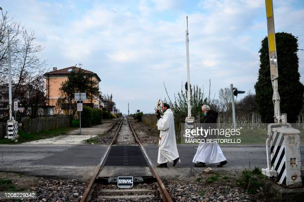 Priests Don Giuseppe Arnaudo , and Don Kresimir Busic, holding a crucifix, cross railway tracks as they conduct a countryside procession to bless...