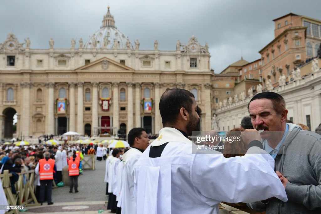 Priests give communion to pilgrims in St Peter's Square after the canonisations of Popes John Paul II and John XXIII on April 27, 2014 in Vatican City, Vatican. Dignitaries, heads of state and Royals from Europe and from around the world attended the canonisations in the Vatican.