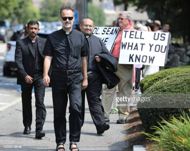 Priests head past protesters to a meeting with Cardinal Sean P O'Malley at St Julia's Parish hall in Weston MA on Aug 28 2018 Jolted by the latest...