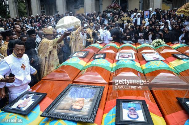Priests hold a ceremony beside coffins of victims of the crashed accident of Ethiopian Airlines during the mass funeral at Holy Trinity Cathedral in...