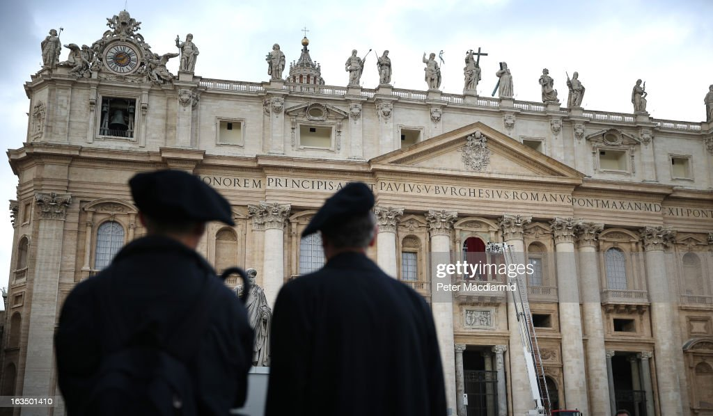 Priests look on as workers install velvet curtains on the main balcony of St Peter's Basilica on March 11, 2013 in Vatican City, Vatican. Cardinals are set to enter the conclave to elect a successor to Pope Benedict XVI after he became the first pope in 600 years to resign from the role. The conclave is scheduled to start on March 12 inside the Sistine Chapel and will be attended by 115 cardinals as they vote to select the 266th Pope of the Catholic Church.