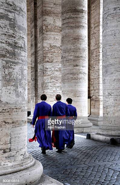 Priests passing through columns at the Vatican