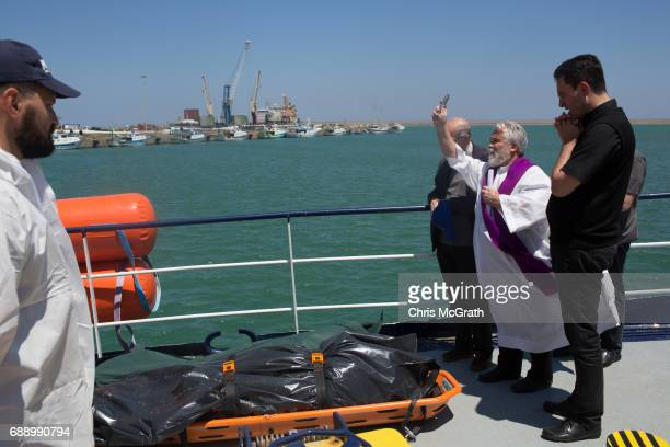 Priests pray over the bodies of migrants that drowned at sea attempting to reach Italy on May 24 on board the Migrant Offshore Aid Station 'Phoenix'...