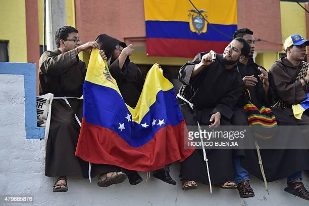 Priests show a Venezuelan flag as they wait for the arrival of Pope Francis before a meeting with the clergy religious and seminarians at the Marian...
