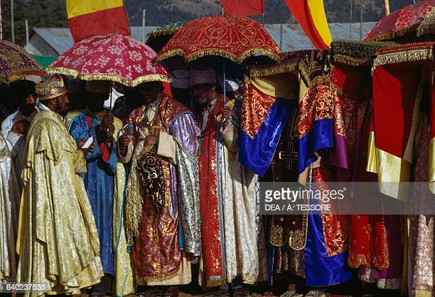 Priests wearing lavish clothes and shading themselves with umbrellas during the Timkat festival Coptic Epiphany Ethiopia