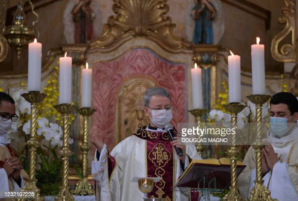 Priests wearing protective face masks as a precautionary measure against the spread of the novel coronavirus, take part in an Easter mass during Holy...