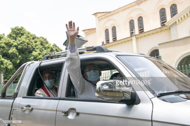 Priests wearing protective masks deliver blessings from a vehicle during Palm Sunday in Caracas Venezuela on Sunday April 5 2020 Amid the coronavirus...