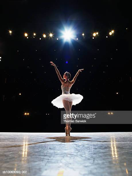 Prima ballerina en pointe on stage, arms raised, rear view