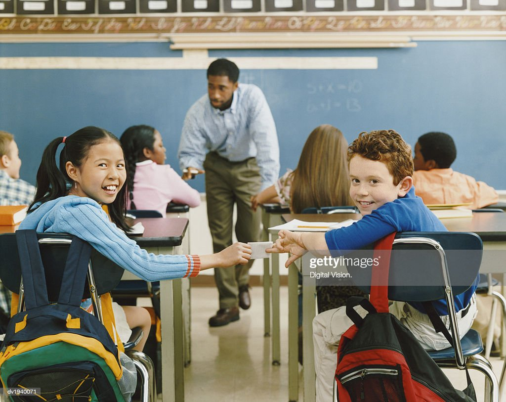 Primary School Boy and Girl Sit at the Back of the Classroom Passing a Note to Each Other : Stock Photo