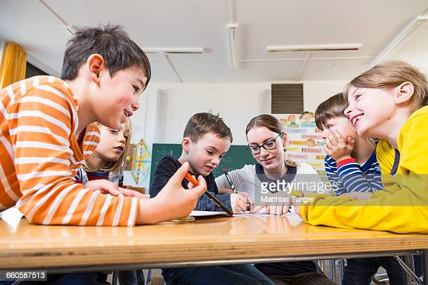 primary school children helping each other