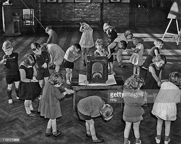 Primary school children performing their own actions to go with a BBC 'Music And Movement' programme on the radio London circa 1935