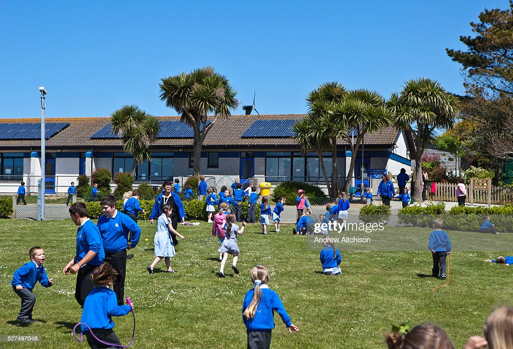 primary school children playing on the grass outside their school during their lunch break the - Images Of Children Playing At School