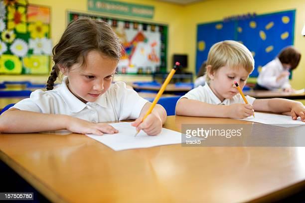 primary school children sitting at their desk's and working - linkshandig stockfoto's en -beelden