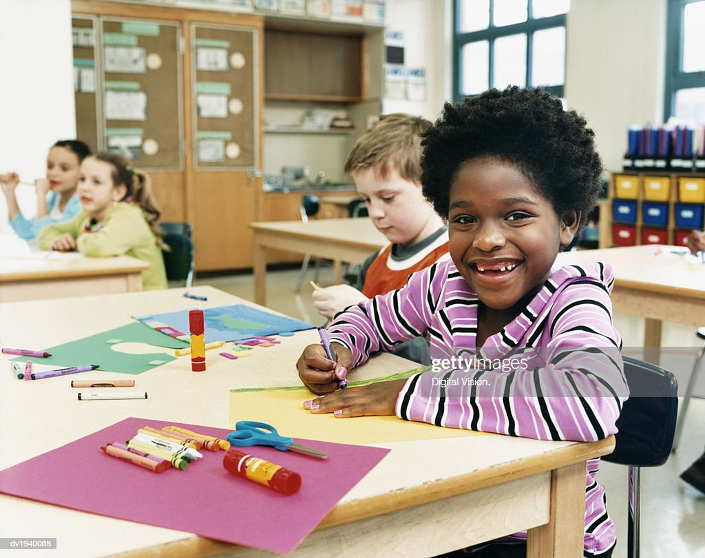 Primary School Children Sitting at Their Desks Colouring-In : Stock Photo