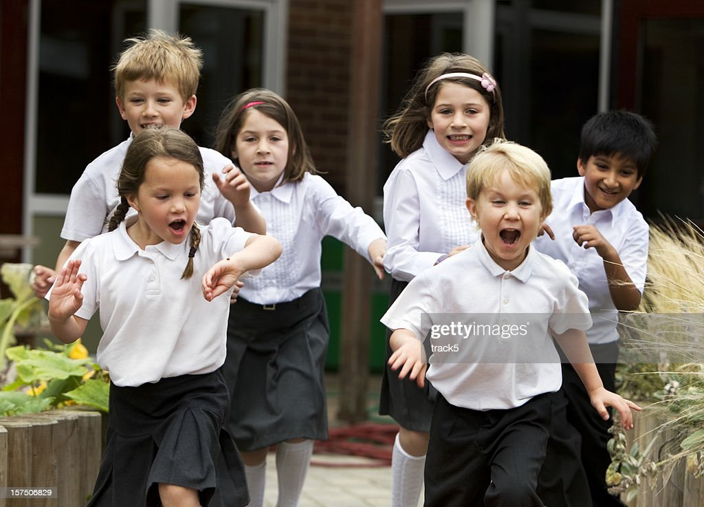 primary school: delighted and excited junior school children leaving class : Stock Photo