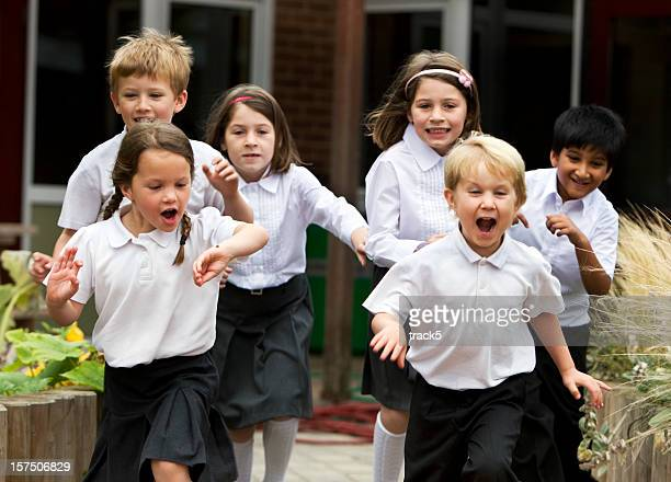 primary school: delighted and excited junior school children leaving class