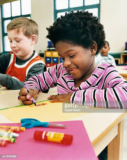Primary School Girl and Boy Sitting at Their Desks Colouring-In