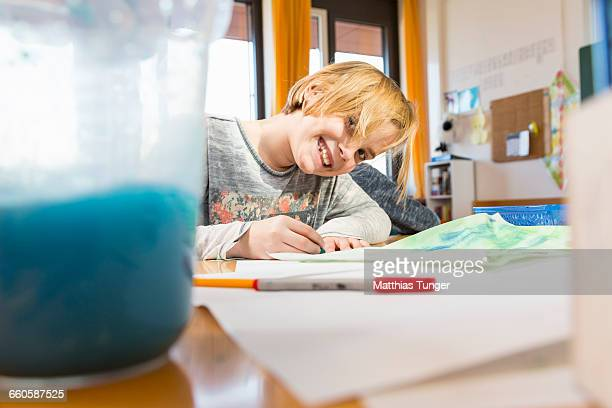 primary school girl painting at a desk