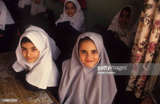 Primary school girls in traditional headscarves sit in a classroom Tehran Iran October 1 1997