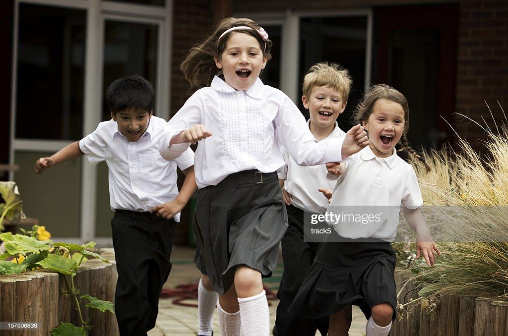 primary school: junior school children running out of their school : Stock Photo