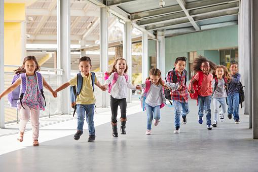 Primary school kids run holding hands in corridor, close up 1031384160