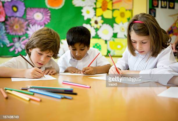 primary school: pupils learning to write in the classroom