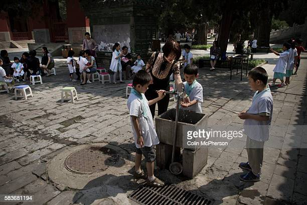 Primary school pupils washing their hands during a break at their school located within the Confucius Temple and Guozijian in Beijing China The...