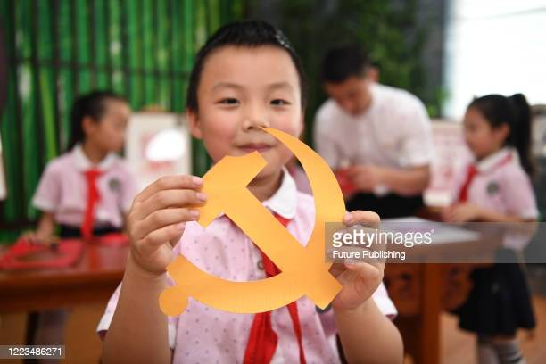 Primary school student displays a handmade Party emblem to celebrate the 99th anniversary of the founding of the Communist Party of China. Guiyang...