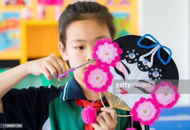 Primary school student makes colorful fan featuring opera mask to welcome the summer solstice on June 19, 2019 in Hohhot, Inner Mongolia Autonomous...